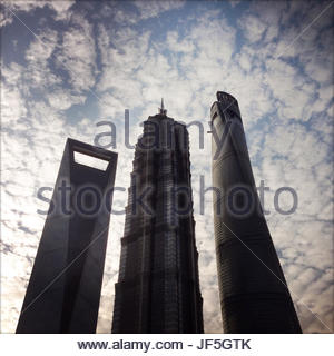 Skyscrapers against a cloud filled sky in central Shanghai. - Stock Photo