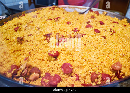 Spanish paella with sausages in a large wok - Stock Photo