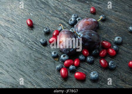 Fresh plums on a dark wooden table - Stock Photo