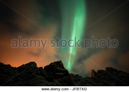 An aurora borealis and the Big Dipper constellation above a mountain peak. - Stock Photo