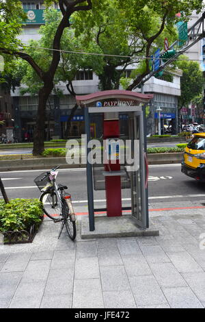 A bicycle parked next to a public phone booth on the curb in Taipei, Taiwan along the street. - Stock Photo