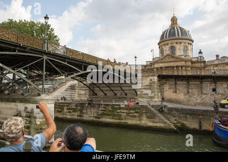 Tourists view the French Institute and the Pont des Arts, or Love Lock Bridge, from a boat cruising the Seine River. - Stock Photo