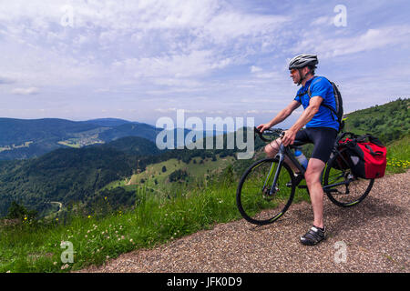 Man sitting on bicycle looking at mountains - Stock Photo