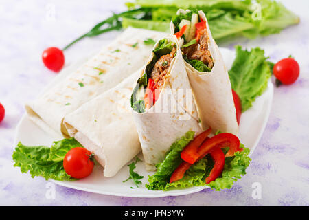 Burritos wraps with minced beef and vegetables on a light background. - Stock Photo