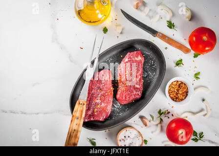 Meat, beef. Fresh raw steaks in a frying pan. Spices (salt, pepper), fresh vegetables - tomatoes, carrots, garlic, - Stock Photo