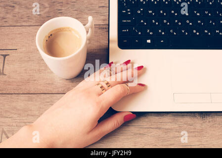 Female working on laptop in a cafe.  White mug of coffee. Close up of a woman hand with rings and long nails, painted - Stock Photo