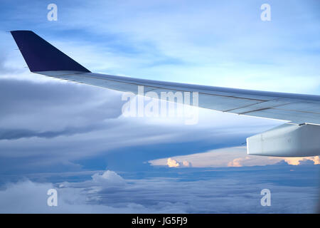 Clouds and sky at sunrise seen through window of an aircraft. - Stock Photo