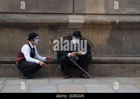 Dresden, Germany. 04th July, 2017. Two street artists dressed up as Charlie Chaplin smoke a cigarette during a break - Stock Photo