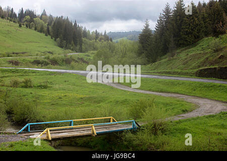 A wooden old bridge over a stream in the valley of the mountain Carpathian road, passing between the hills. - Stock Photo