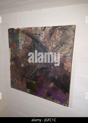 Abstract painting hanging on a white brick wall - Stock Photo