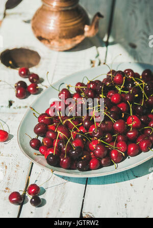 Plate of fresh ripe sweet cherries on rustic light blue wooden garden table, selective focus, vertical composition. - Stock Photo