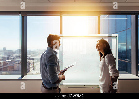 Two business colleagues working on a business plan. Business investors writing their ideas on whiteboard during - Stock Photo