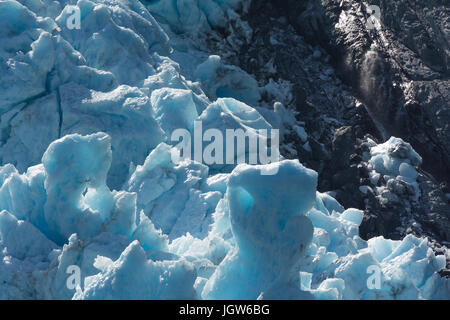 Blue glacier ice pushes up against crumbling black rock - Stock Photo