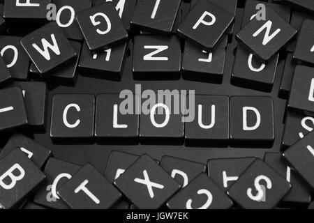 Black letter tiles spelling the word 'cloud' on a reflective background - Stock Photo