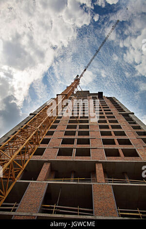 The new house that is being built, and the tower crane, rest against the blue sky with light clouds and touch the - Stock Photo