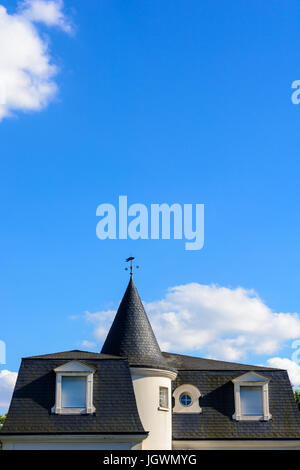Slate roof of a high standing house with a turret and closed shutters under a blue sky. - Stock Photo