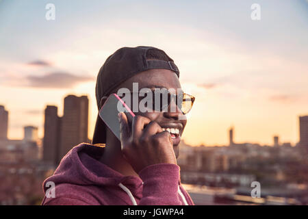 Young man making smartphone call at sunset roof party in London, UK - Stock Photo