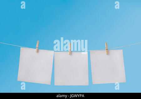 Three squares of note paper for messages, pegged to hang on washing line against a blue sky.  Left blank to provide - Stock Photo