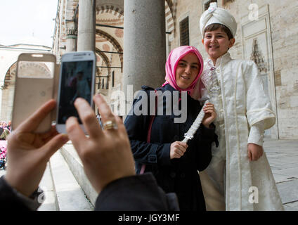 Young turkish boy in the ceremonial circumcision outfit posing with his mother outside the the Blue mosque, Sultanahmet, - Stock Photo