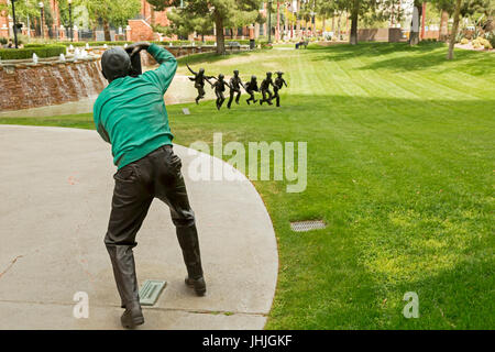 Phoenix, Arizona - A sculpture of a photographer photographing a sculpture of children playing in the park in front - Stock Photo