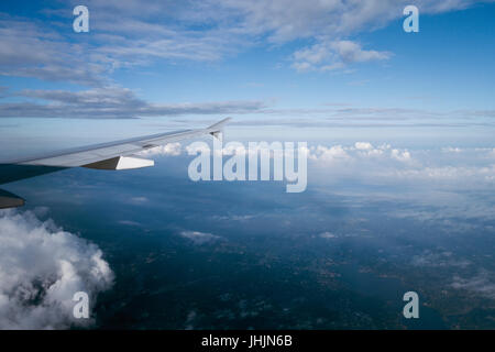 above the clouds flying high on airplane window view - Stock Photo