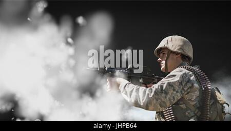 Digital composite of Soldier man holding a weapon against black background with clouds - Stock Photo