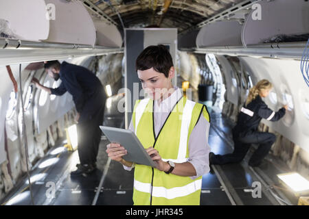 Female aircraft maintenance engineer using digital tablet in an aircraft at airlines maintenance facility - Stock Photo