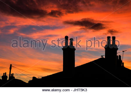 London UK. 15th July 2017. Chimneys and rooftops are silhouetted against a beautiful summer sunset in Wimbledon - Stock Photo