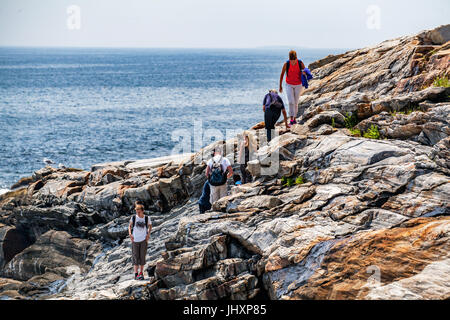 A vacationing family climbs rocks along the coast of Pemaquid Bay at Bristol, Maine, USA. - Stock Photo