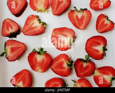Strawberry creative pattern. Isolated food backdrop. Sliced ripe red berry with green leaves on white background - Stock Photo