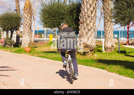 Man riding a bicycle and having fun outdoor. Summer holiday adventure traveler. - Stock Photo