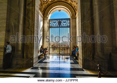 Tourists at the gate from inside St Peters Cathedral at Vatican City with the area of Rome Italy - Stock Photo