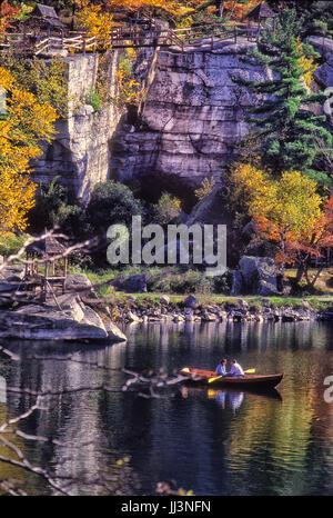 Romantic couple in boat. Man and woman in row boat during Autumn, yellow and orange leaves on tree, rocky background. - Stock Photo