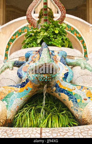 colourful statue of lizard inlaid with beautiful staied glass with flowing water and plants around in Park Guell, - Stock Photo