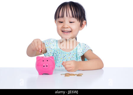 Asian Chinese little girl putting coins into piggy bank in isolated white background - Stock Photo