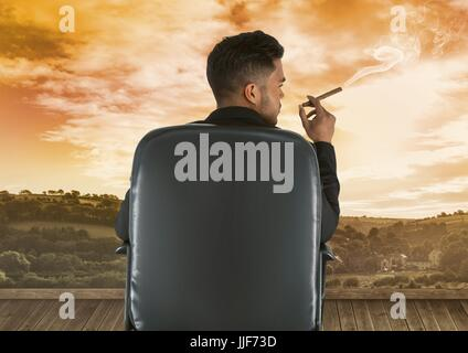 Digital composite of Businessman sitting on chair and smoking cigar against sky - Stock Photo