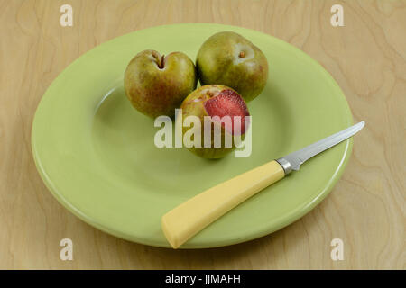 Plum apricot hybrid plums in green plate with knife on wooden table - Stock Photo