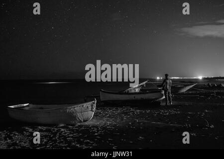 Man in the middle of the boats looks at the starry sky - Stock Photo