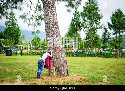 Thimphu, Bhutan - Aug 29, 2015. A woman praying at the sacred tree in Thimphu, Bhutan. Bhutan is a small country - Stock Photo
