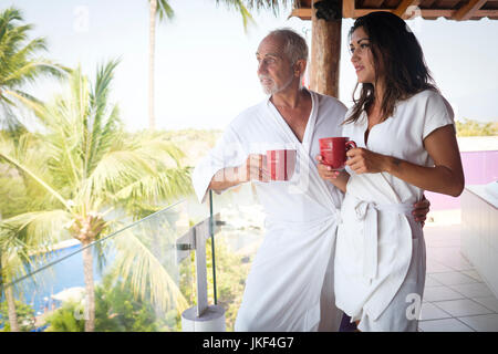 http://n450v.alamy.com/450v/jkf4g7/young-woman-and-older-man-drinking-coffee-in-bathrobes-on-balcony-jkf4g7.jpg