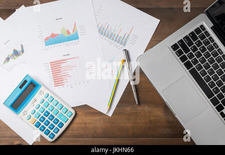 business accessories (notebook, calculator, planchette, tablet, pencil, pen) and graphics, tables, charts on white - Stock Photo