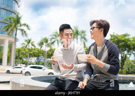 Two businessman having a casual meeting or discussion in the city. - Stock Photo