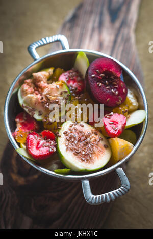 Fruit salad with flax seeds in a tin bowl on a wooden stand vertical - Stock Photo