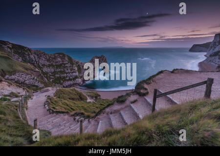 Dorset, UK. 27th July, 2017. The moon over Durdle Door on the Jurassic Coast in Dorset at sunset. Credit: Rich Dyson/Alamy - Stock Photo