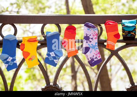 Various colorful children socks hanging on a washing line outdoors. Many little socks on a clothesline for kids - Stock Photo