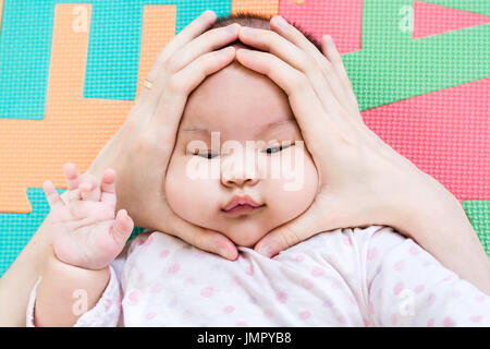 Hands of mother squeezing on face of her cute little baby on the eva foam in bedroom - Stock Photo