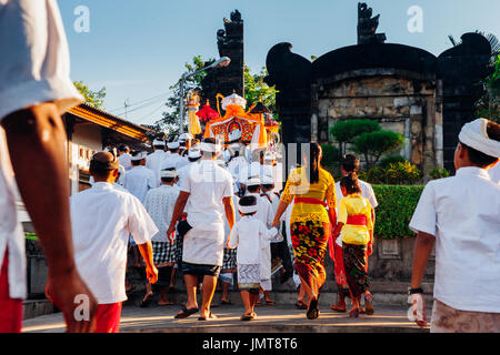 Bali, Indonesia - March 07, 2016: Balinese people in traditional clothes carry jempana or wooden litter at the procession - Stock Photo