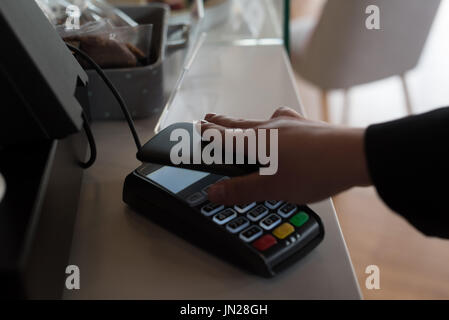 Cropped hand on customer playing bill through smart phone at checkout counter in cafe - Stock Photo