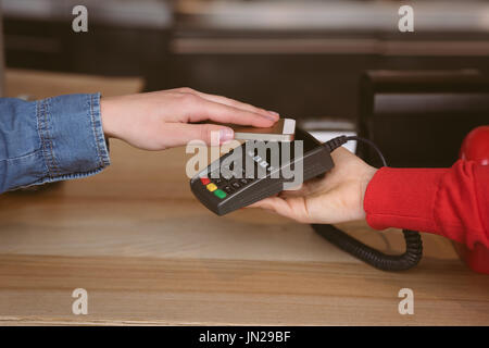 Close-up of woman paying bill through smartphone using NFC technology in cafe - Stock Photo