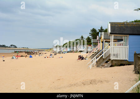 Summer beach scene with the famous painted wooden beach huts at Wells-next-the-sea Norfolk England - Stock Photo